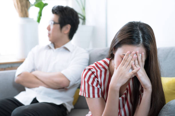 An Asian wife is crying on the sofa after an argument with her husband behind her. An Asian wife is crying on the sofa after an argument with her husband behind her. asian couple arguing stock pictures, royalty-free photos & images
