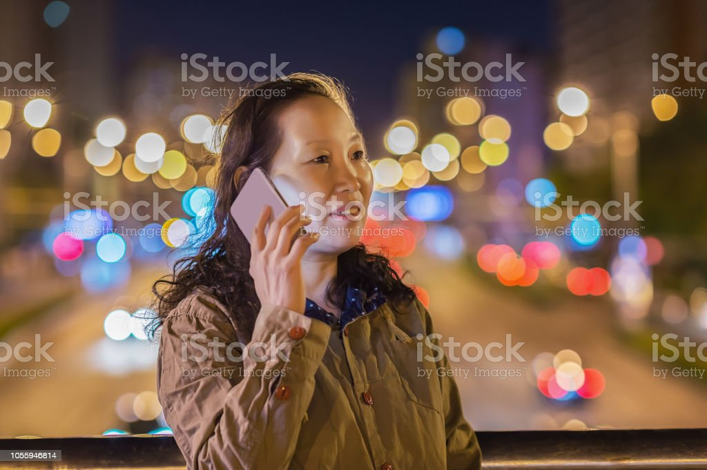 An asian woman calling by mobile phone in the city night stock photo