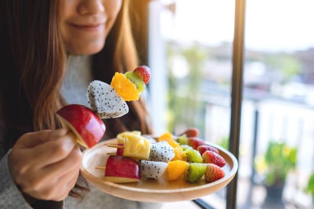 eine asiatische Frau hält und isst eine frische gemischte Früchte auf Spießen – Foto