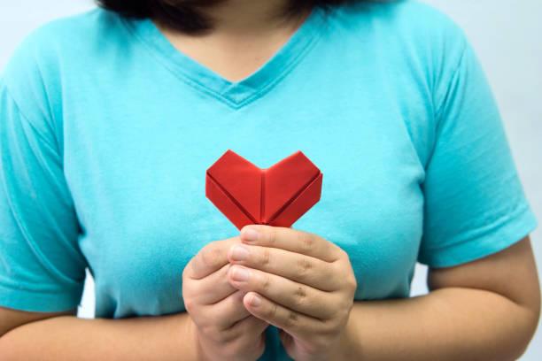 eine asiatische frau hält herz origami vor ihrer brust. eine frau, rotes herz papier an jemanden. liebe und konzept für den valentinstag zu geben. - besondere geschenke stock-fotos und bilder