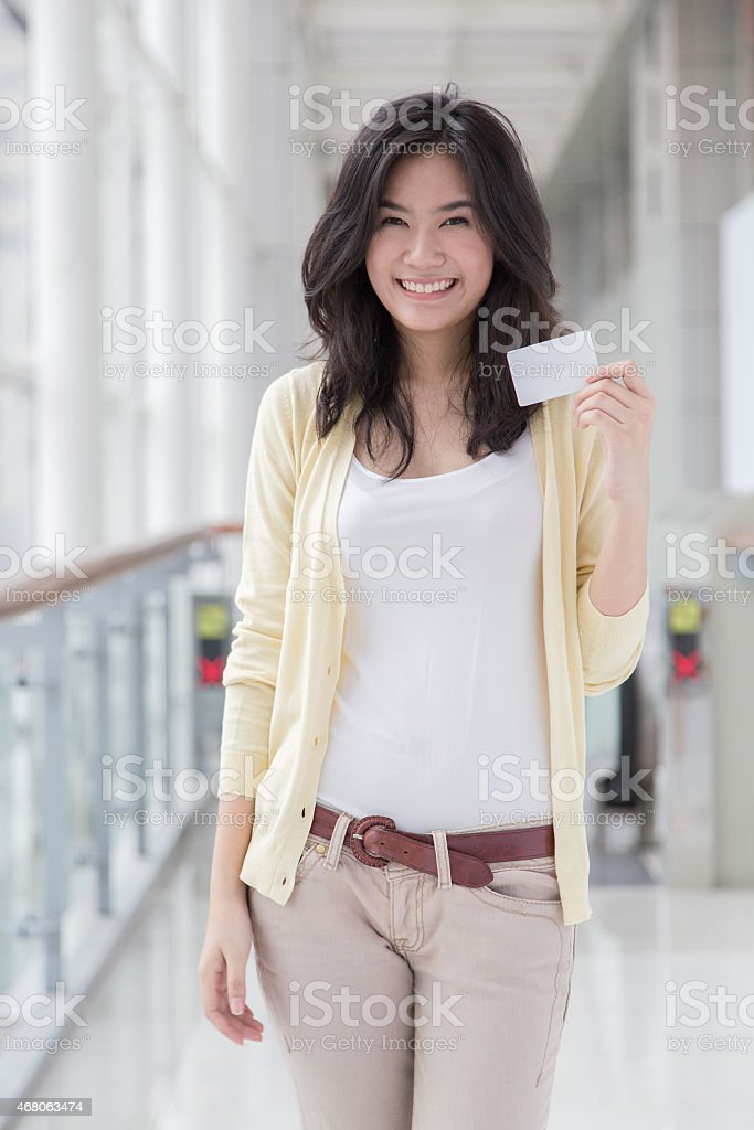 An Asian woman in a yellow cardigan smiling with a card stock photo