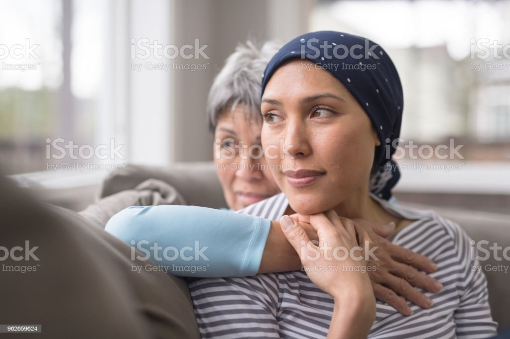An Asian woman in her 60s embraces her mid-30s daughter who is battling cancer stock photo