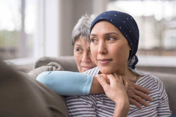 An Asian woman in her 60s embraces her mid-30s daughter who is battling cancer An ethnic woman wearing a headscarf and fighting cancer sits on the couch with her mother. She is in the foreground and her mom is behind her, with her arm wrapped around in an embrace, and they're both looking out the window in a quiet moment of contemplation. headscarf stock pictures, royalty-free photos & images