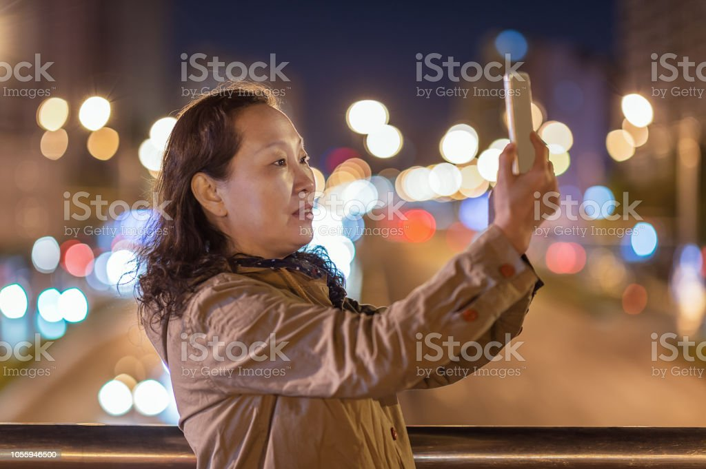 An Asian woman is taking a photo with her mobile phone at night in the city stock photo