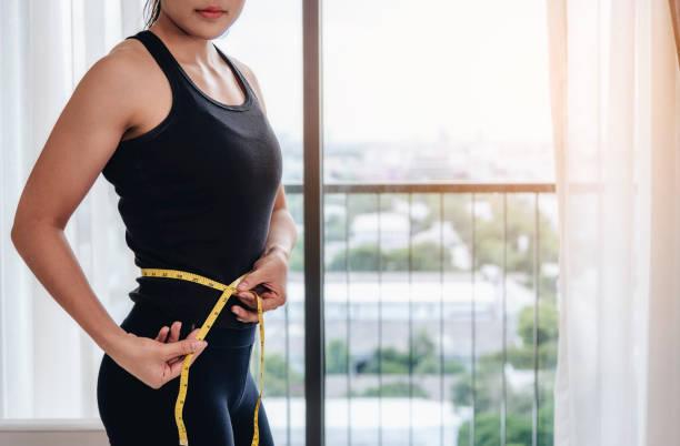 Eine asiatische Frau verwenden eigene Messung Hüftgurte. Um die Größe und Form von sich selbst nach dem Training zu steuern. – Foto