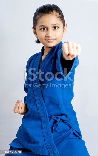 Sweet little girl training punch and attack in plastic action like karate kid isolated on white background
