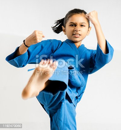 Asian girl posting Taekwondo fighting on white background