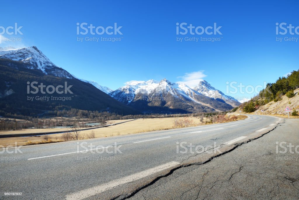 An asphalt road in French Alps mountains close-up. Parc Ecrins