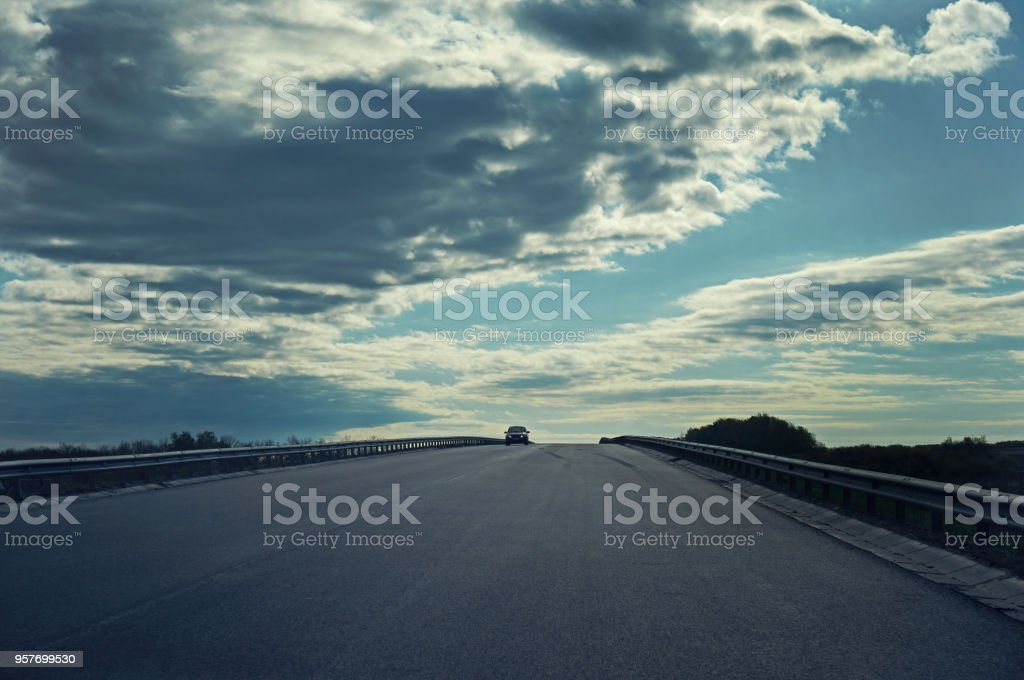 An asphalt road with a car against the sky with clouds.