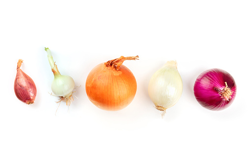 An assortment of various types of onions, shot from the top on a white background with copy space