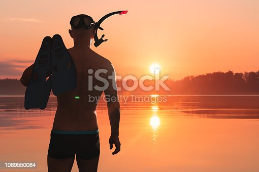 An athletic man with a swimming mask, snorkel and flippers enters the lake. He is going to do freediving