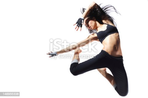 istock An athletic woman jumping up to strike a fierce pose 146955338