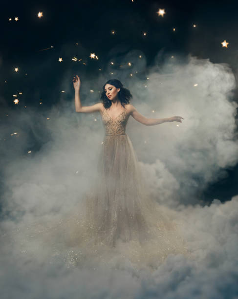 an attractive goddess stands in the clouds in a luxurious, gold, sparkling dress. whimsical hairstyle. against the backdrop of a star and space. artistic photography - romantic moon stock photos and pictures