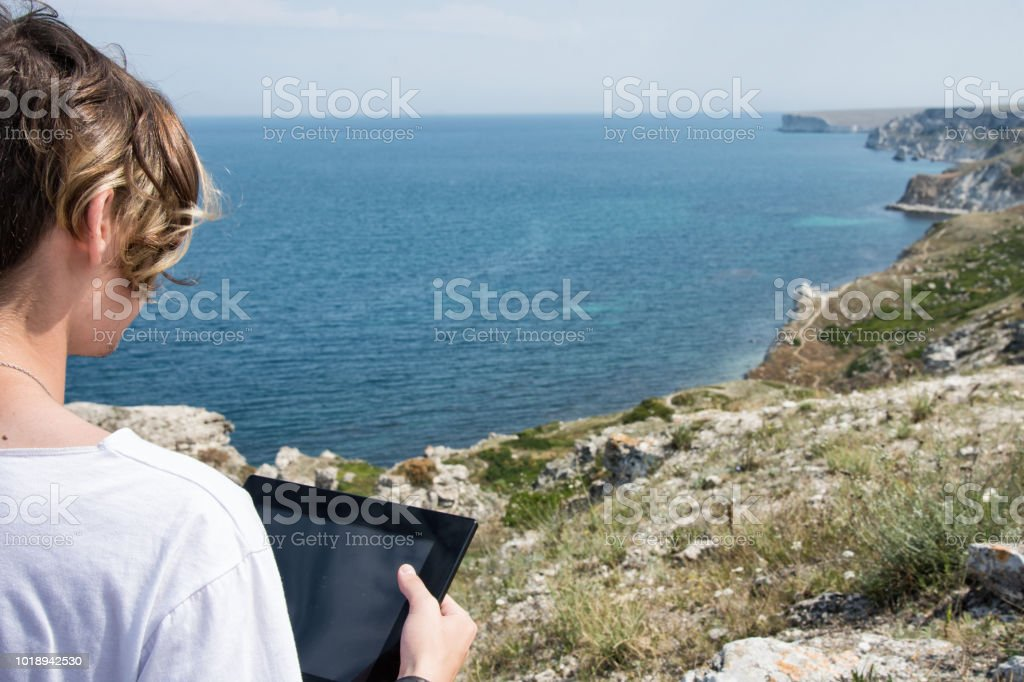 An attractive guy and a tablet. Sea and vacation.