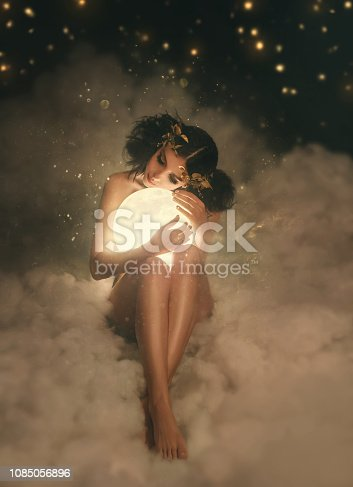 An attractive, naked goddess sits in the clouds, hugs the moon. A whimsical hairstyle with an unusual decoration in the Greek style. A beautiful, refined body. Artistic Photo