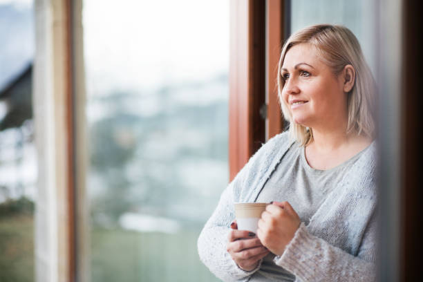 An attractive overweight woman at home, holding a cup of coffee. stock photo