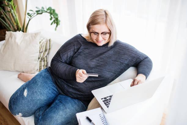 eine attraktive übergewichtige frau zu hause, online-zahlungen. - damen jeans übergrößen stock-fotos und bilder
