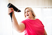 An attractive overweight woman with hair dryer at home, having fun.