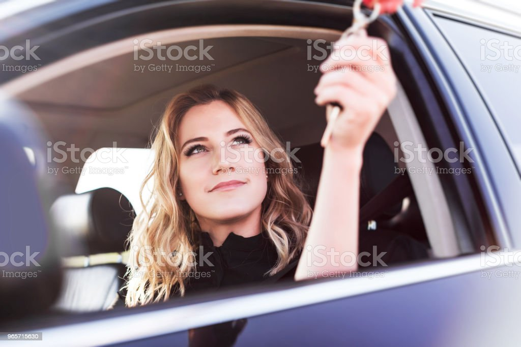An attractive woman in a car gets the car keys. Rent or purchase of auto - Royalty-free Adult Stock Photo