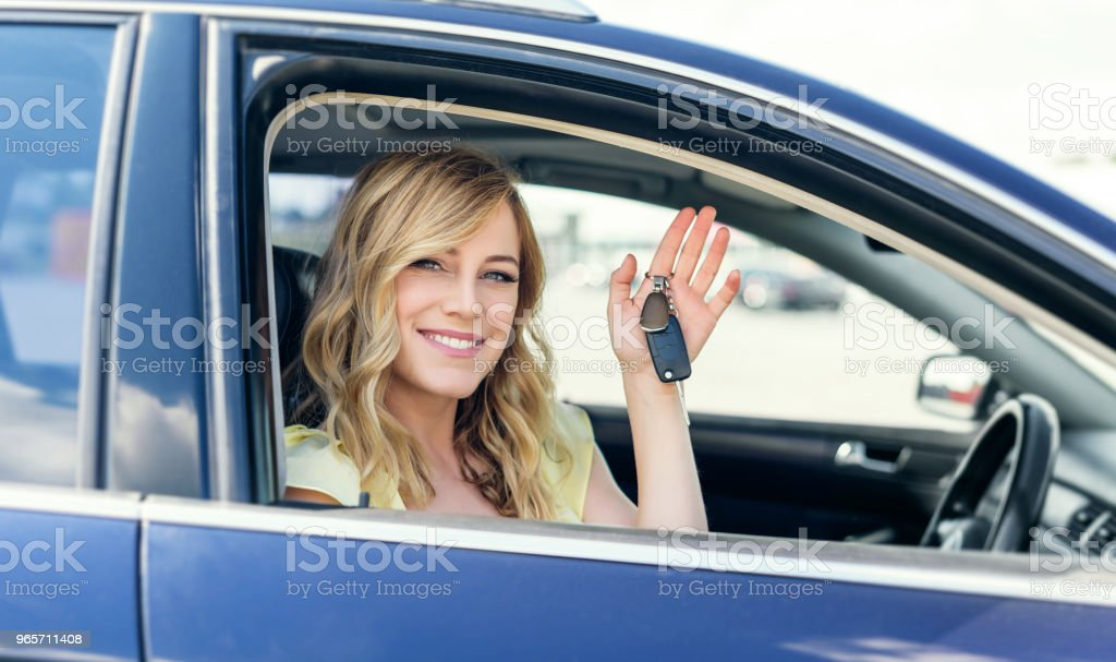An attractive woman in a car holds a car key in her hand - Стоковые фото Автомобиль роялти-фри