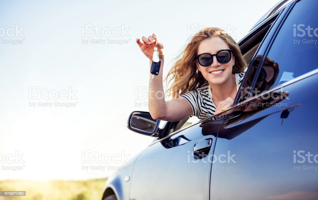 An attractive woman in a car holds a car key in her hand An attractive woman in a car holds a car key in her hand. Rent or purchase of auto - concept. Adult Stock Photo