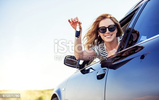 istock An attractive woman in a car holds a car key in her hand 970371780