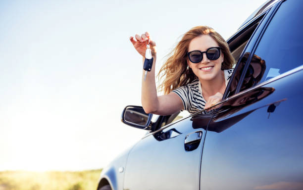 An attractive woman in a car holds a car key in her hand stock photo