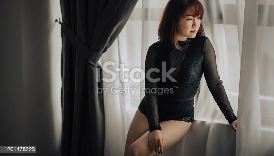 506435758 istock photo an attractive young chinese female with lingerie sitting at the window edge looking away 1201478223