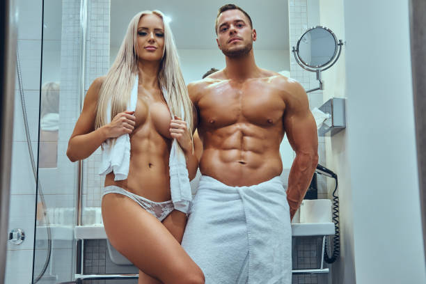 An attractive young couple in stylish twin bathroom. stock photo