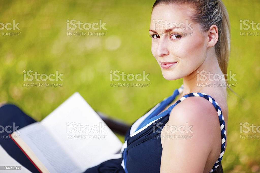 An attractive young female sitting with book in a park royalty-free stock photo