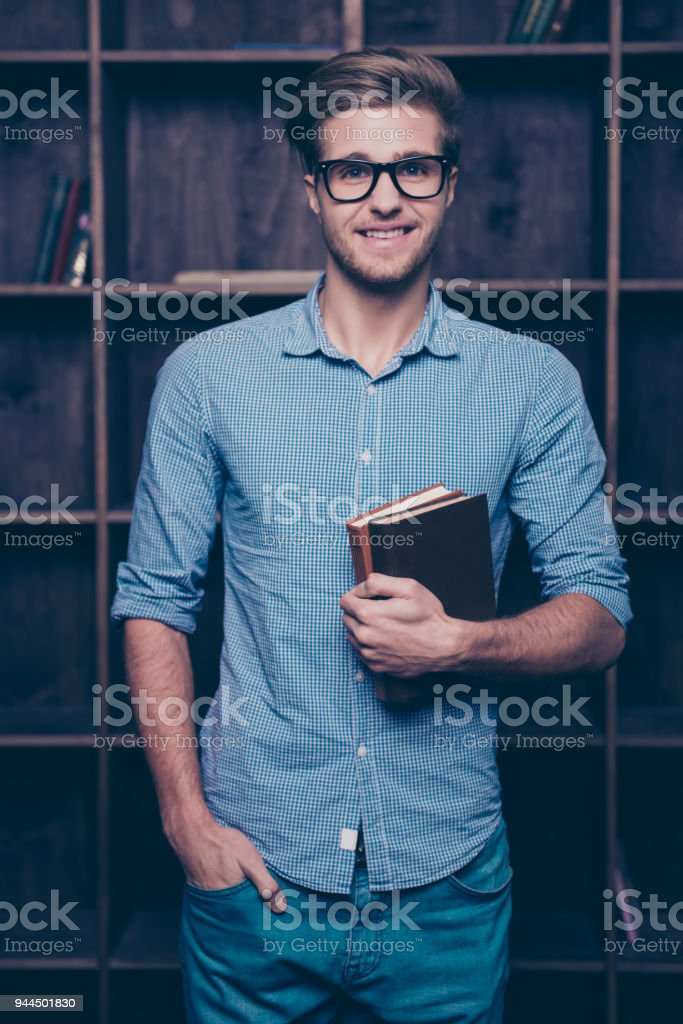An attractive young guy in glasses standing in front of shelves,  holding books and keeping his hand in a pocket stock photo