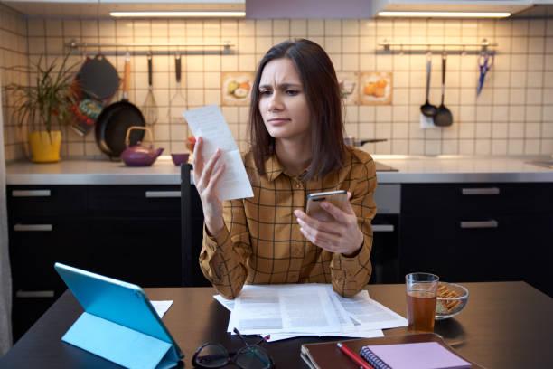 Eine attraktive junge Hausfrau trägt ein Hemd zu Hause und Gas- und Stromrechnungen untersucht. grimmig sieht Ausgaben in diesem Monat und ist unter Stress, wenn Konten zu überprüfen. – Foto