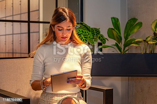 A young hispanic lady, smartly dressed in business casual clothes,  is seen occupied with her digital tablet while waiting in an office lobby to be called in for her appointment. Image shot in ambient light; horizontal format.