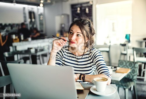 An attractive young woman sitting in a coffee shop with a cup of coffee, thinking.