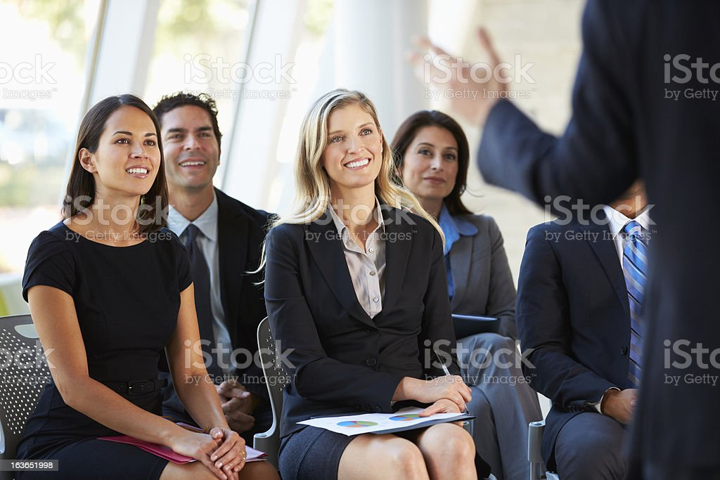 An audience of business people smiling at a presenter stock photo