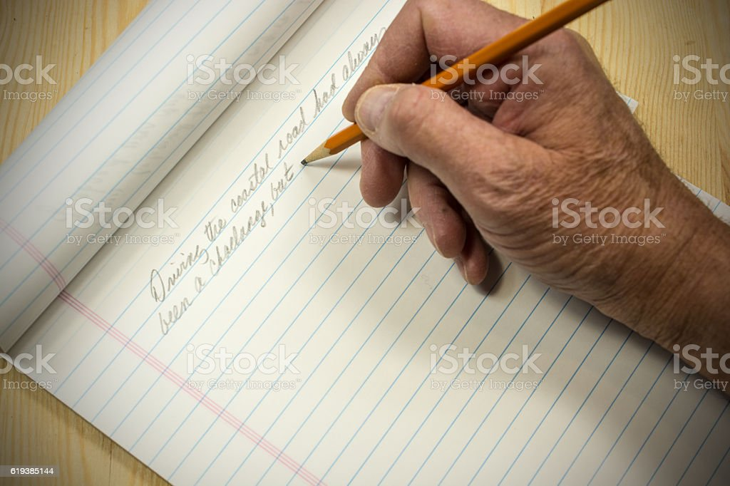 An author beginning his manuscript with pencil and pad stock photo