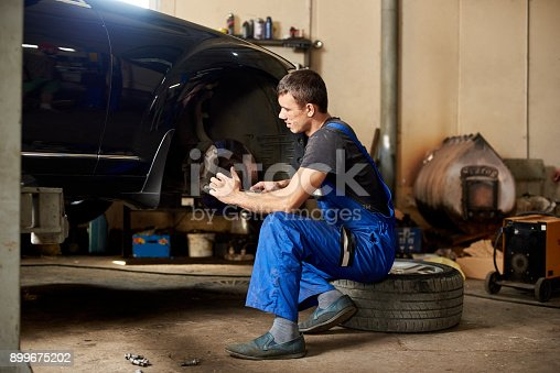962888586 istock photo An auto mechanic in a dirty work uniform repairs front wheel of car in the garage. The guy looks carefully at the problem 899675202