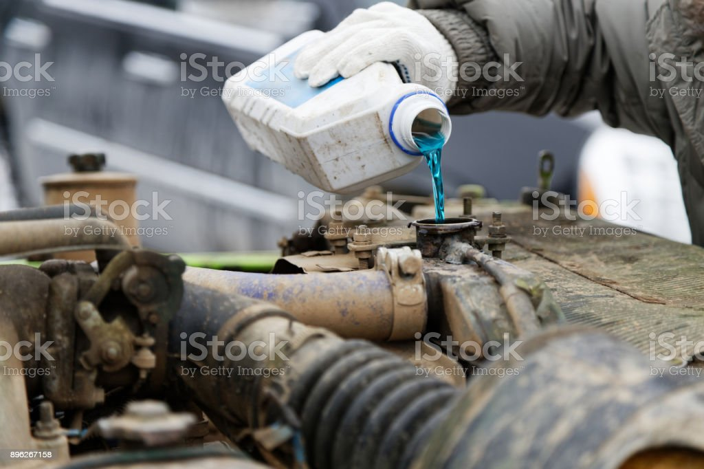 An auto mechanic pours antifreeze into the radiator of an old car engine stock photo