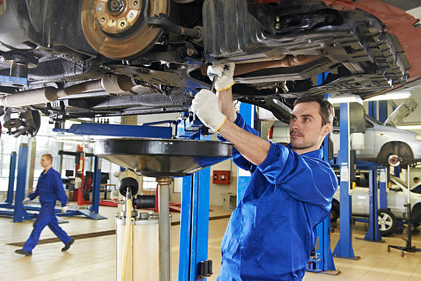 An auto mechanic repairing the suspension on a car stock photo