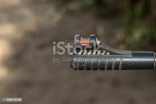1048647890 istock photo an automatic riffle gun aim in the darkness 1135815290