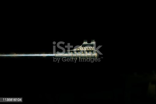 1048647890 istock photo an automatic riffle gun aim in the darkness 1135816104