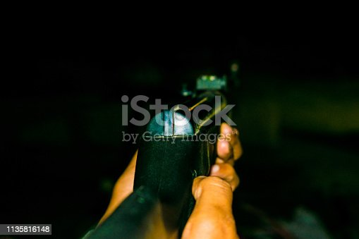 1048647890 istock photo an automatic riffle gun aim in the darkness 1135816148