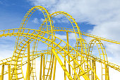 Yellow rollercoaster track with blue sky in the background.