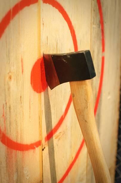 un hacha clavada en un objetivo de madera - bota fotografías e imágenes de stock