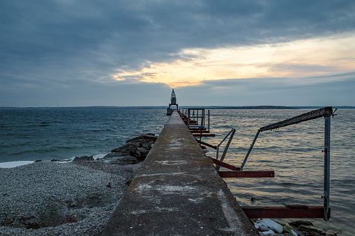 An big old crane at the end of an pier with a pave leading to the end of the pier