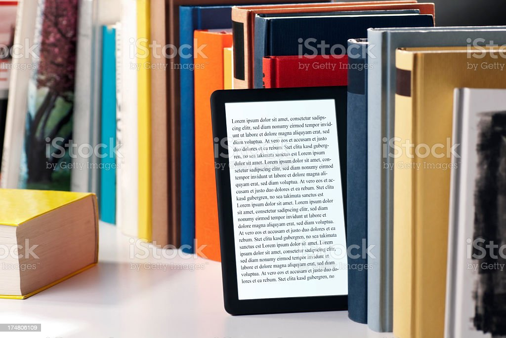 An e book tablet reader tucked in a book shelf stock photo