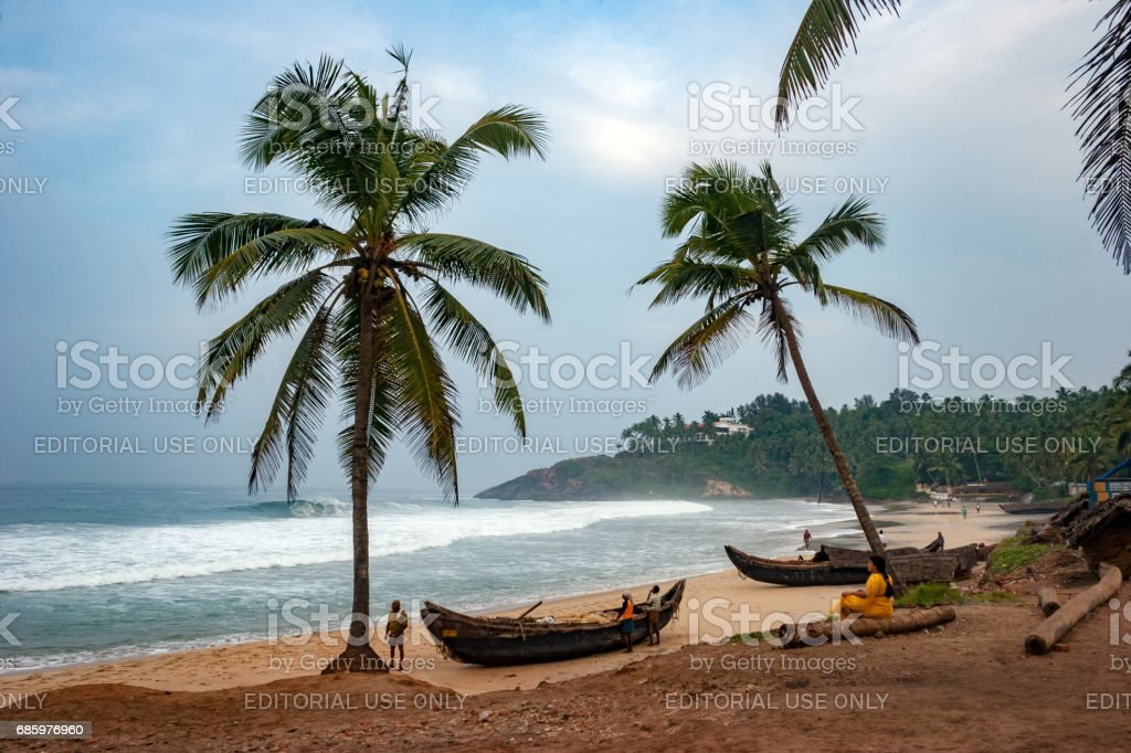 An early morning view with some unidentified people at Kovalam beach, stock photo