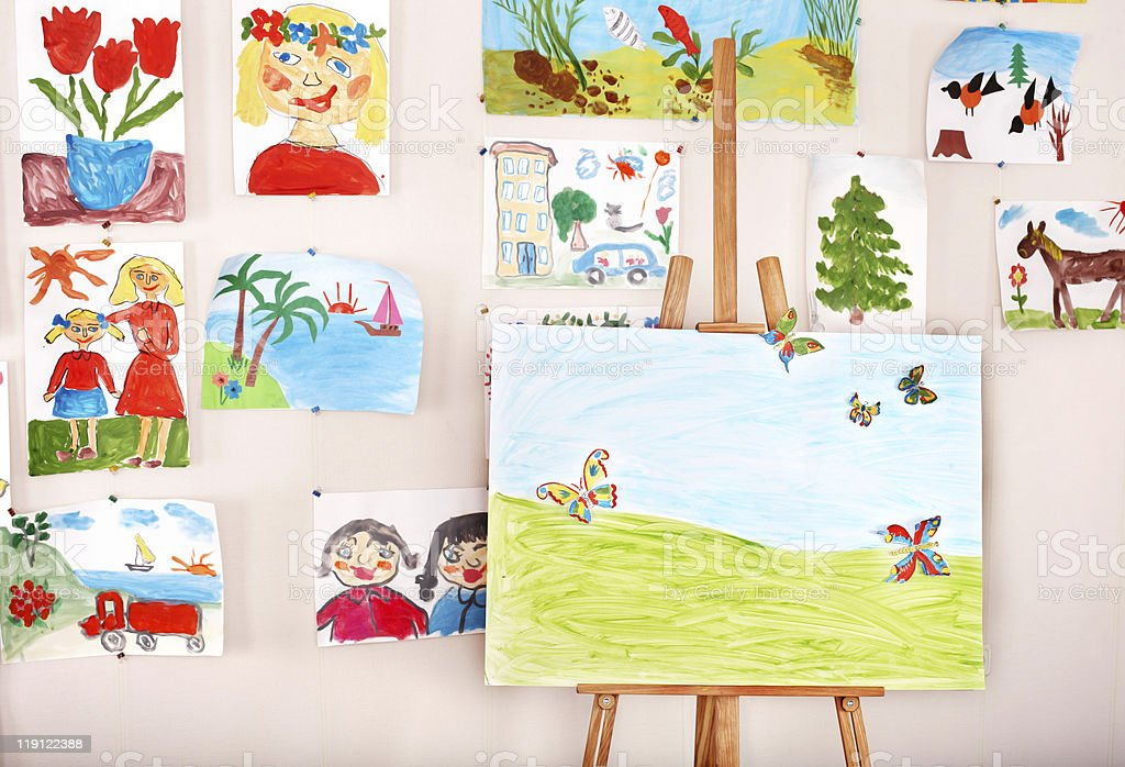 An easel surrounded by artwork made by children in art class stock photo