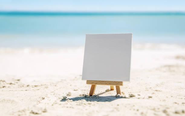 Eine Staffelei mit einer rein weißen Leinwand am Strand des Ozeans. – Foto