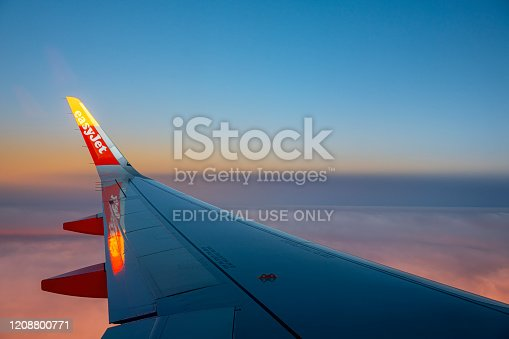 An EasyJet aircraft wing flying over Southern England on route to Morocco. In the background are the vibrant colours of a sunset through clouds.